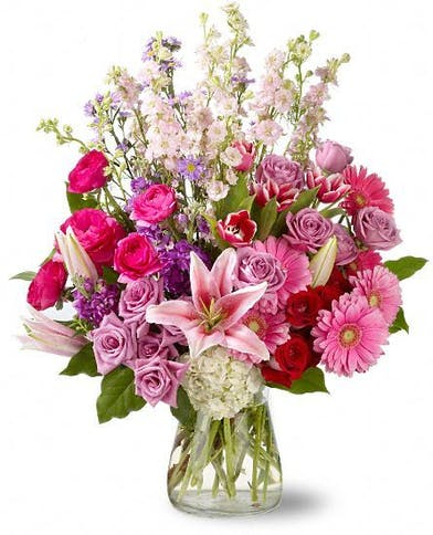 Fresh flowers in pretty shades of pink, red, white and purple create a sweet symphony of color in this stunning floral arrangement that's two feet tall, and just as wide
