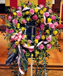 A stunning tribute featuring pink and yellow roses with lovely assorted greens