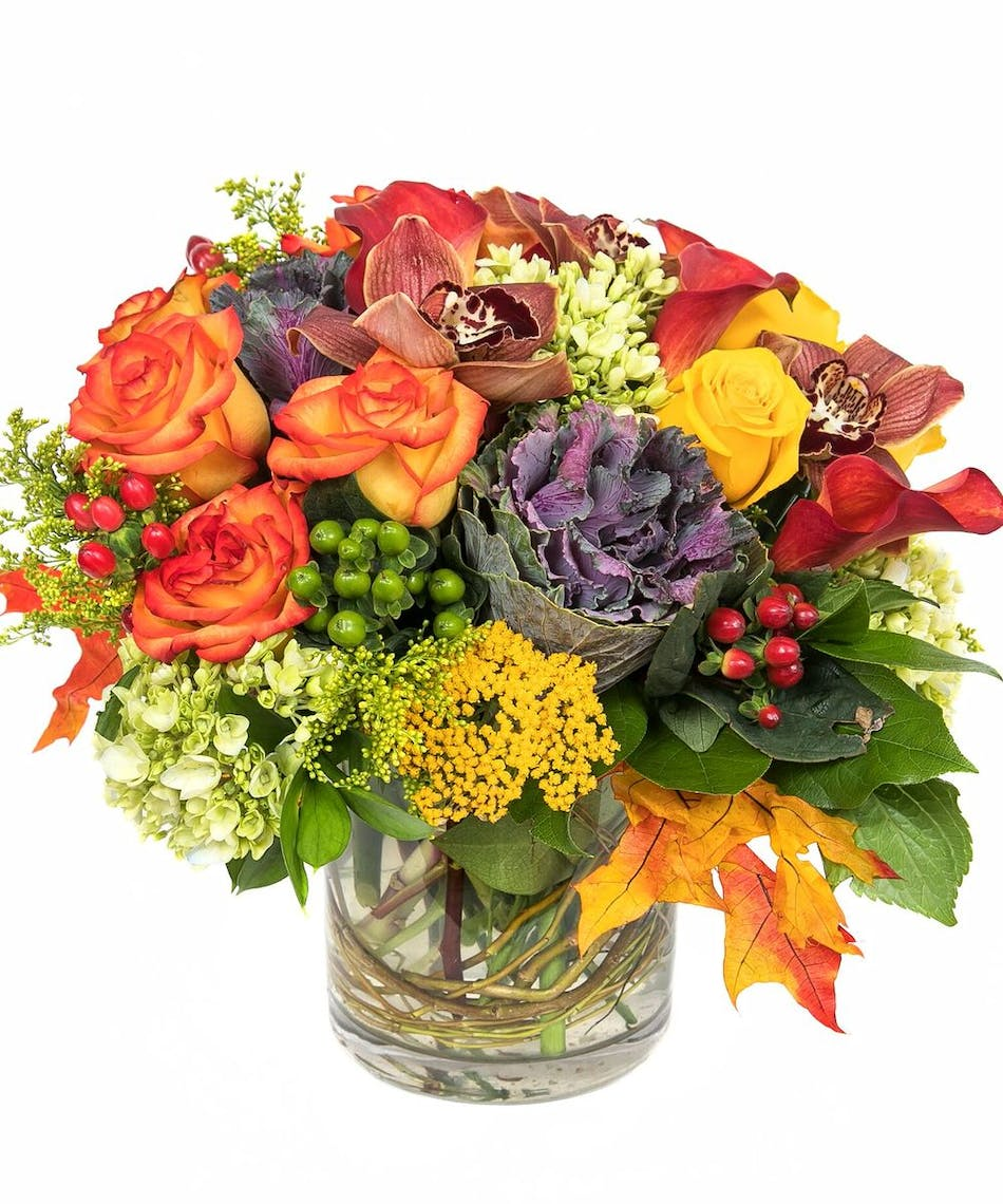 Features roses in red and orange along with red and green hypericum and green hydrangeas – skillfully designed in a cylinder vase with curly willow tips and leaves.