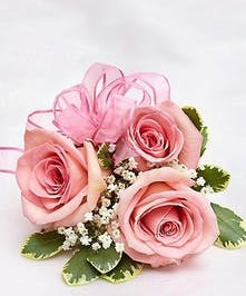 Beautiful hand-designed wrist corsage arrangement of pink roses, accented with fresh greenery